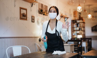 Young woman with face mask working indoors in cafe, disinfecting tables