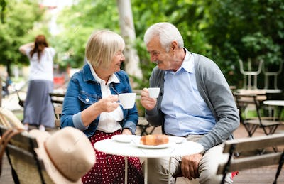 Happy senior couple in love sitting outdoors in cafe, talking