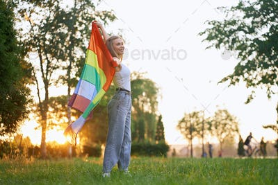 Smiling woman holding rainbow lgbt flag behind back