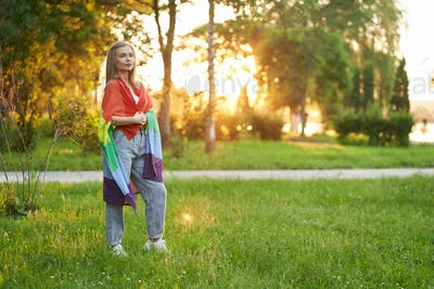 Tolerant woman holding lgbt flag on shoulders