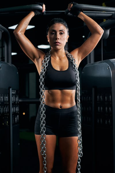 Female bodybuilder posing with chains on neck