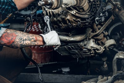 bearded male repairing engine of a car in a garage.
