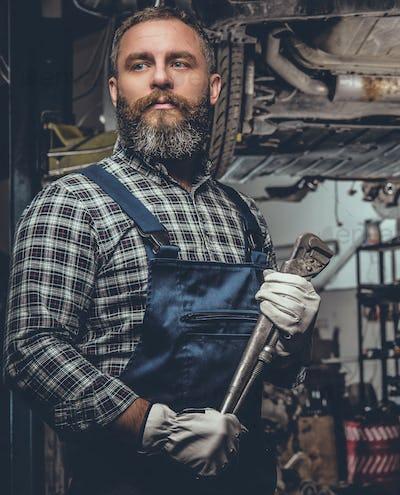 Bearded mechanical male in a garage.
