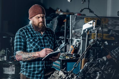 Bearded mechanics male inspecting car.
