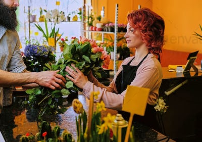 Bearded male gives roses bouquet to a redhead female in a market
