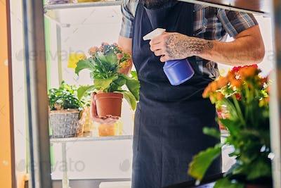 A man watering flowers in a pot.