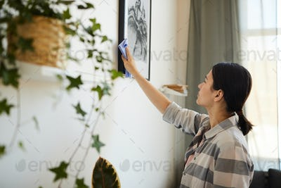 Woman wiping the dust from picture