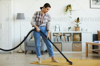 Housekeeper vacuuming the carpet