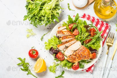 Grilled chicken with fresh salad at table