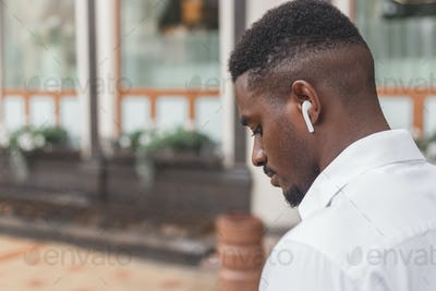 Close-up image of a guy in a profile listening to music via earbuds
