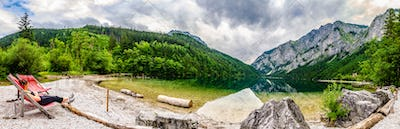 Landscape panorama with woman on sunbed next to the lake Leopoldsteinersee,Styria,Austria. Travel