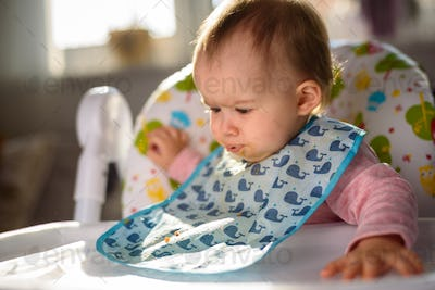 Baby not liking the food and spits it out. Sitting in a high chair in bright living room. 6- 12