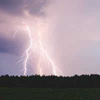 Dramatic lightning bolt at night over rural area. Agriculture fields