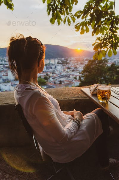 Young woman siting with glass of beer looking at sunset over city Graz in Austria
