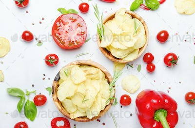 Unhealthy food background, potato chips with salt, tomatoes, chili and bell pepper