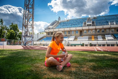 Smiling girl in orange sportswear sitting on stadium's field of