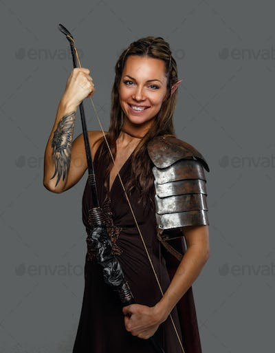 Smiling warrior woman holds bow.