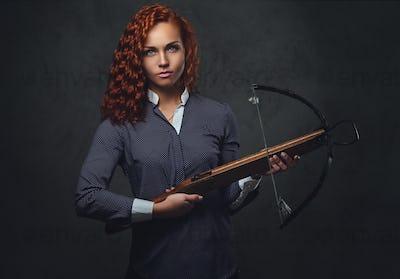 Redhead female  holds crossbow.