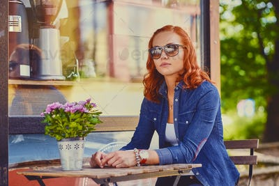 Redhead female drinks coffee in a cafe.