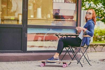 Redhead girl drinks coffee after skating on Longboard.