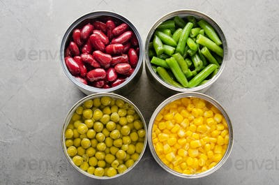 Flat lay view at canned kidney beans, green beans, peas and corn in opened tin cans