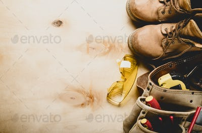 Construction concept background of toolbelt yellow boots goggles ant tools on plywood flat lay