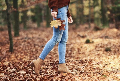 Low section of woman walking in autumn forest