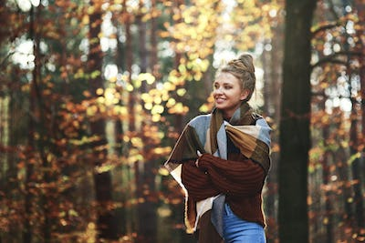 Beautiful young woman walking in the autumn forest