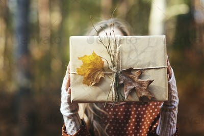 Close up of woman's hands holding gift in autumn forest