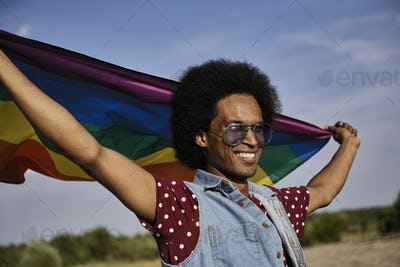 Young African man with rainbow flag standing at beach
