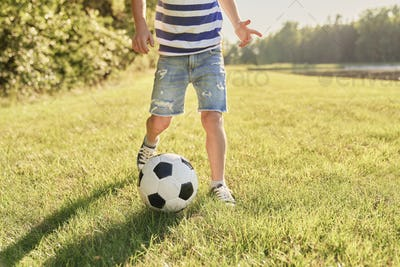 Little boy playing football on the grass