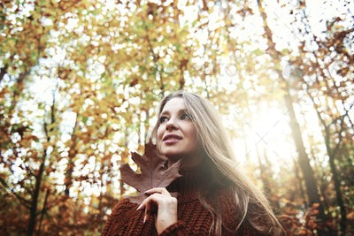 Beautiful  young woman holding autumnal leaf