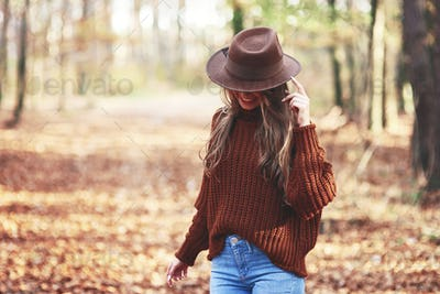 Gorgeous young woman wearing warm clothes in autumn woods