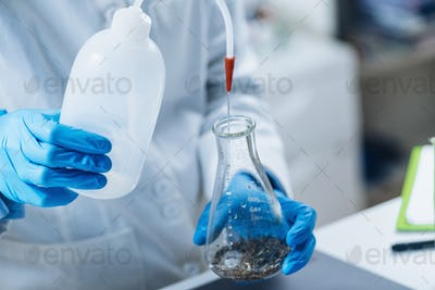 Pesticides in Tea. Quality Control Inspector Working with Herbal Tea Sample in Laboratory