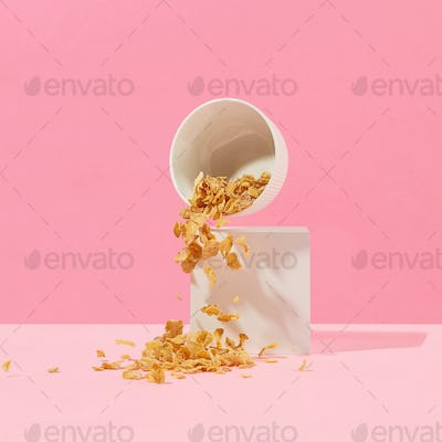 cornflakes fall out of a white bowl