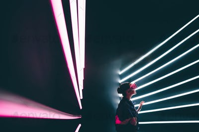 Girl using VR goggles in colorful neon lights,