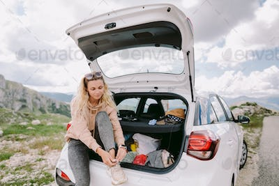 happy woman travel by car in mountains on vacation