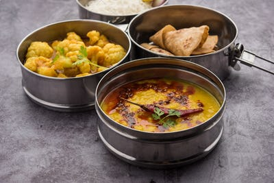 Indian Lunchbox or Tiffin includes Cauliflower Masala, Dal Fry, Rice, Chapati and salad