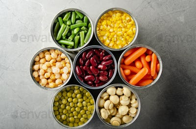 Flat lay view at canned vegetables in opened tin cans on kitchen table