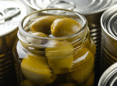 Canned green olives in just opened glass mason jar. Non-perishable food
