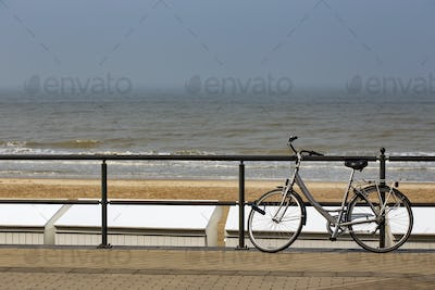 Parked bicycle on a fence near the sea