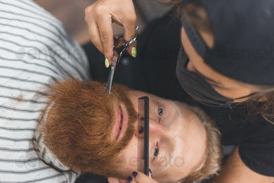 A man at a barbershop. Woman barber clipping mustache. Barber woman in mask.