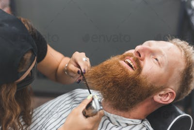 A man at a barbershop. Woman barber clipping beard and mustache. Barber woman in mask.