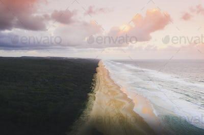 Drone view of coastline under a pastel pink sky