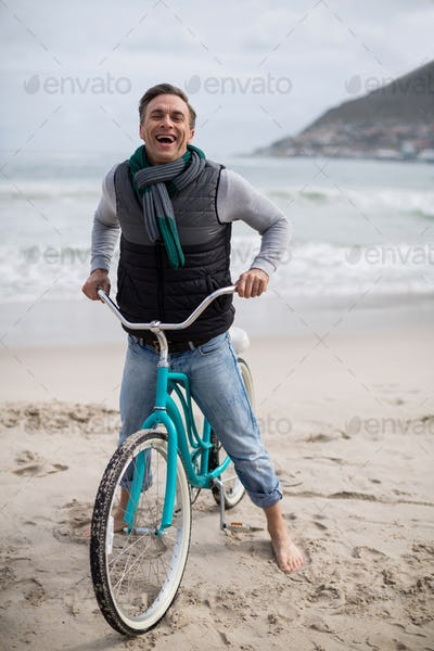 Portrait of mature man riding bicycle on the beach