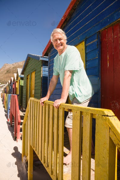 Portrait of smiling senior man standing at beach house