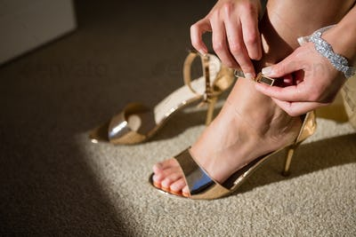 Low section of bride trying on sandals at home
