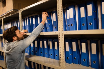 Businessman taking file from shelf in storage room