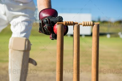 Close up of wicket keeper standing by stumps during match