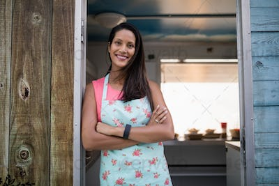 Portrait of happy waitress standing with arms crossed
